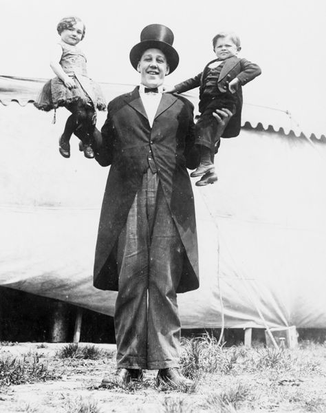 side show Johaan Aassen a circus performer from the Al G. Barnes Amusement Co holding a dwarf in each hand 1923